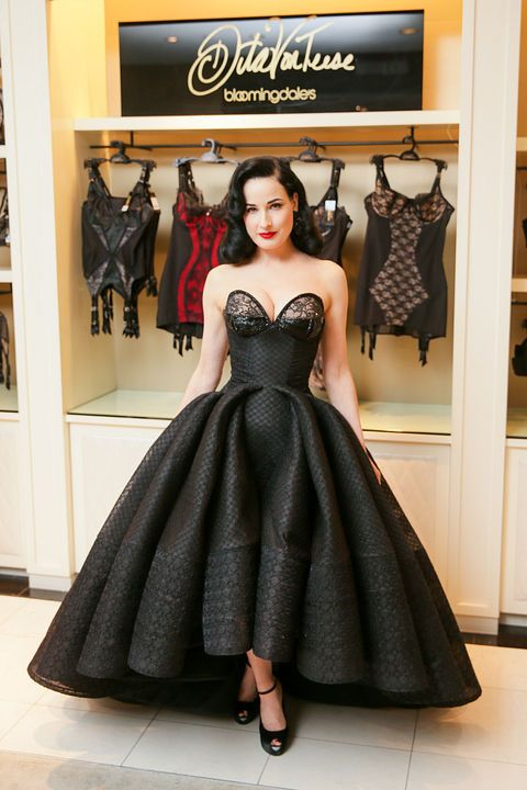 Glamorous Dita von Teese in front of her new line of women's lingerie at the opening party. As usual, her gown is exquisite!