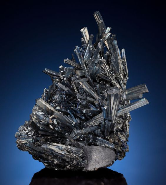 "STIBNITE Wuning Mine, Qingjiang, Wuning Co., Jiujiang Prefecture, Jiangxi Province, China  Here a ""jackstraw"" grouping of dark grey Stibnite crystals exhibits metallic luster with blue iridescent highlights."