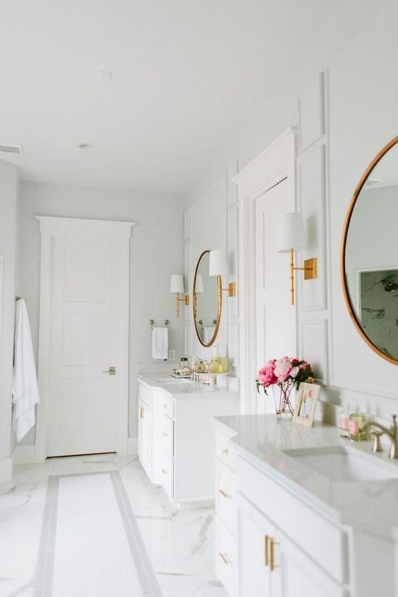 Stunning all-white master bathroom with gray and white carrara marble flooring, brass wall sconces with lamp shades, round vanity mirrors with gold frames, bright brass sink faucets, gray marble counter tops and classic traditional white cabinets. #whitebathroom #luxury #bathroomdesign #carrara #serene