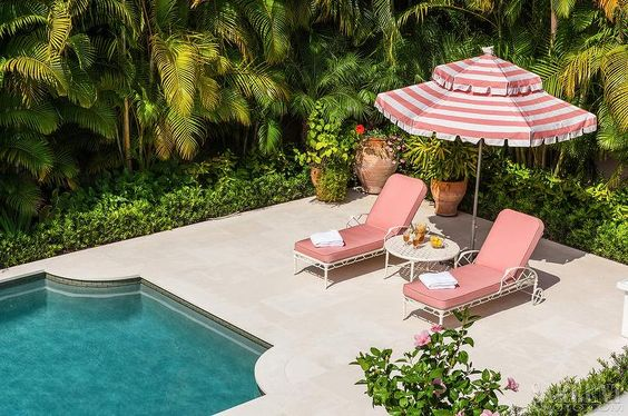 Hollywood regency patio features a pair of white bamboo loungers lined with salmon pink cushions shaded with a white and pink striped umbrella placed in front of an art deco pool.: