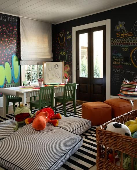 Westbrook Interiors    fun, whimsical play room design with black chalkboard painted walls, gray silk roman shades, Ikea Stockholm Rand white & black striped rug, white & black striped ticking floor cushions, white table, green chairs and orange pillows.