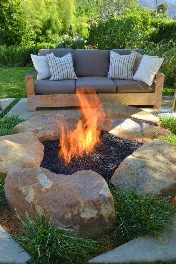 aménagement jardin moderne avec canapé en bois et foyer à feu ouvert