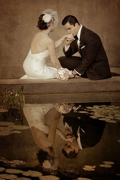 With the bride and groom reflected on the water, this romantic photo is straight out of a fairy tale.