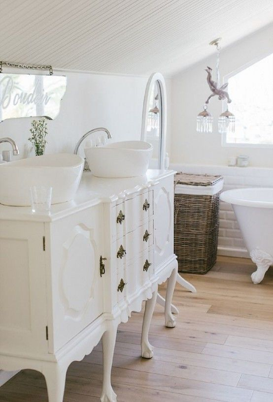 A repurposed dining room buffet is painted white and used as a bathroom vanity with vessel sinks. in a cottage style bathroom. Come check out Antique Vintage Style Bathroom Vanity Inspiration! #bathroomdesign #bathroomvanity #classicstyle #traditionaldecor #interiordesignideas