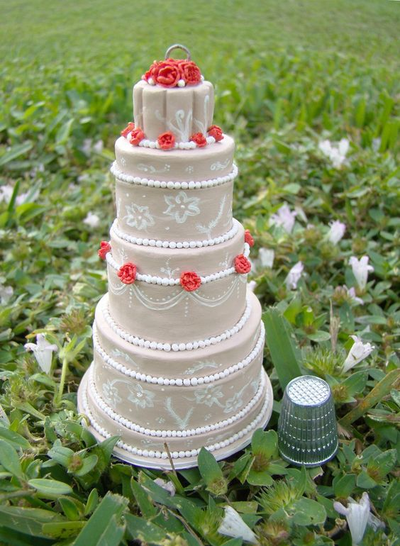 I want one of these!  Send them a picture of your wedding cake, and she will make an ornament that looks EXACTLY like it!