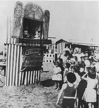 Weston Super Mare, England. Punch and Judy is a traditional, popular puppet show featuring Mr. Punch and his wife, Judy. The performance consists of a sequence of short scenes, each depicting an interaction between two characters, most typically the violent Punch and one other character. It is often associated with traditional English seaside culture.