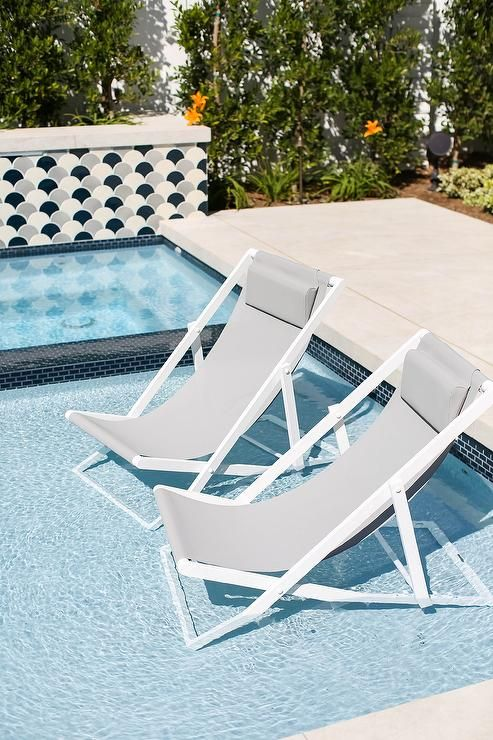 White And Gray Pool Loungers Sit On A Tanning Ledge In An In