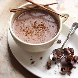 In a 3 1/2- to 4-quart slow cooker, combine milk, half-and-half, chocolate pieces, coffee powder, 1 teaspoon cinnamon, and ground chipotle chile pepper.