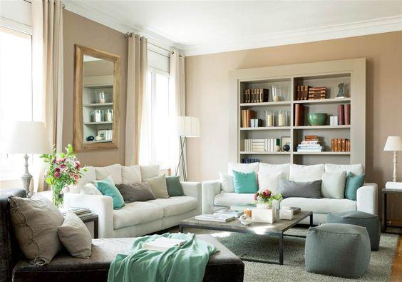 Salón con sofá blanco y cojines y plaids azules, verdes y grises