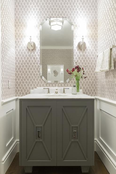 Lovely powder room features top half of walls clad in gray print wallpaper and bottom half of walls clad in wainscoting lined with a gray vanity with trim moldings topped with white marble under a octagon frameless mirror illuminated by glass and nickel sconces.