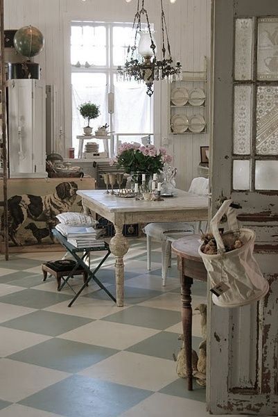 A beautiful grey and white French Country kitchen with checkered floors, rustic farm table, and vintage chandelier. #frenchcountry #countrykitchen #romanticdecor