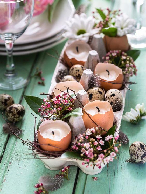 Une boîte à œufs et des coquilles bougeoirs