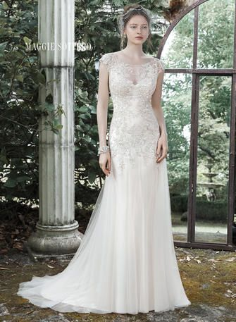A dramatic illusion back and illusion bateau neckline, adorned with glimmering metallic lace appliques, make a statement in this glamorous A-line wedding dress, accented with lovely tulle skirt. Finished with covered buttons over zipper closure.  Maggie Sottero Bridal - 5MN711-Sundance