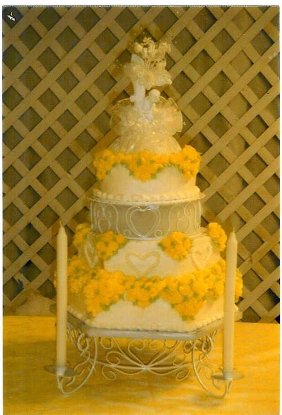 Yellow roses on each corner of a hexagon shape cake on candlelight wedding cake stand