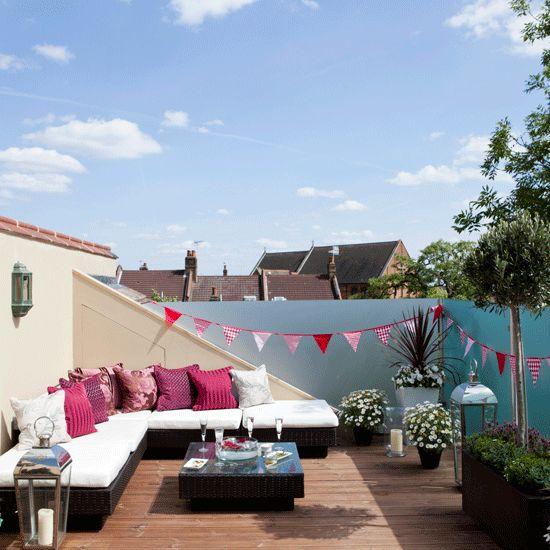 Inspiración deco de terraza con cojines de colores y guirnaldas de tela.