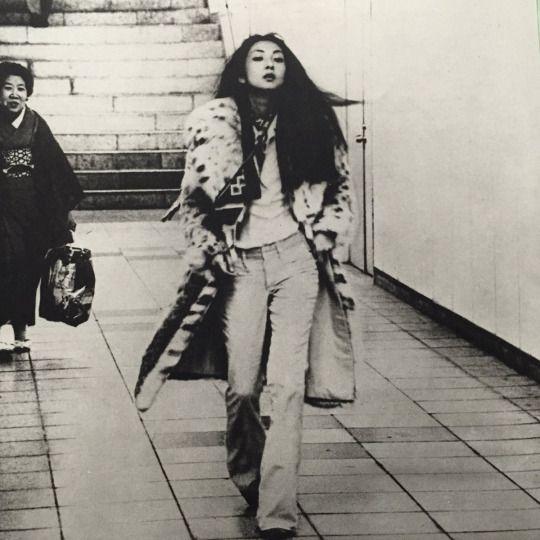 ロングコートにベルボトムのデニムを履いて歩く梶芽衣子の画像