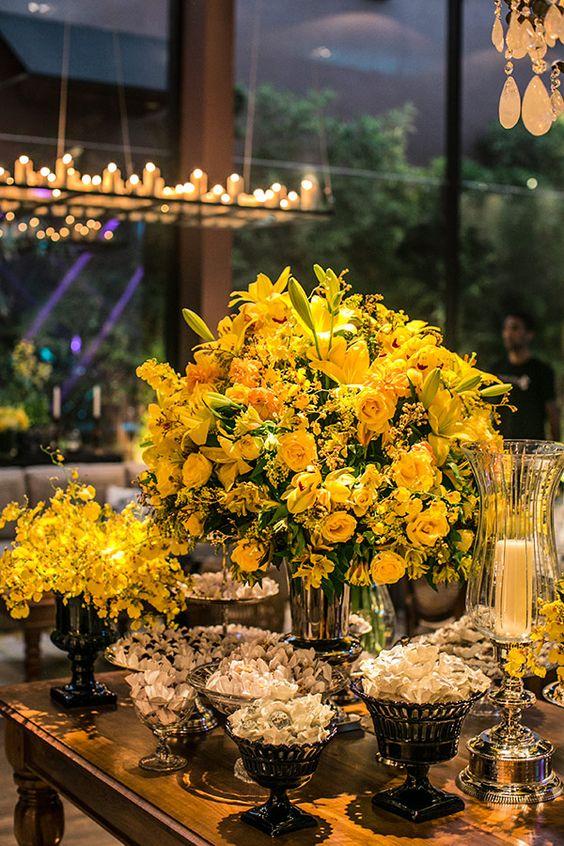 Mesa de doces com arranjos de flores amarelas  Casamento clássico