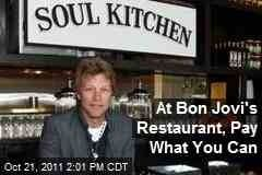 """Jon Bon Jovi opens 'pay what you can' restaurant The Jon Bon Jovi Soul Kitchen in New Jersey hopes to provide those living on a prayer with a cheap alternative to fast food   Going down in a blaze of Jon Dory … Jon Bon Jovi at his Soul Kitchen in New Jersey. Photograph: John W Ferguson/Getty Images Sean MichaelsView all 100 comments Jon Bon Jovi is opening a new """"pay-what-you-can"""" restaurant, hoping to give low-income families an alternative to unhealthy fast food.  The Jon Bon Jovi Soul Kitchen opened on Wednesday in Red Bank, New Jersey, near the singer's hometown of Sayreville. After two years of serving meals in various locations, the """"community kitchen"""" has set up a permanent location in a 1,100 sq ft former garage. While customers are welcome to pay for their meals, those who are, er, living on a prayer may instead work as volunteers. """"Picture the coolest brasserie in your hometown, that's what this is,"""" Bon Jovi told New York magazine. """"It's the hottest-looking restaurant in this town.""""  Indeed, this is hardly a soup kitchen. The bistro's opening menu includes rainbow beet salad, pork chops with fig and apple chutney, and homemade carrot cake with lemon cream cheese frosting. Everything is """"organic, healthy, good-for-you food"""", Bon Jovi said, but don't expect to find him behind the stove. """"I'm an expert at washing dishes, but I can cook less than zero.""""  """"At a time when one in five households are living at or below the poverty level, and at a time when one out of six Americans is food insecure, this is a restaurant whose time has come,"""" Bon Jovi said. """"This is a place based on and built on community – by and for the community."""":"""