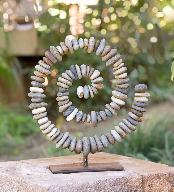 This Stone Spiral sculpture makes a wonderful statement piece for the home that appreciates the natural beauty of river rock. The metal inner construction is a sturdy base for the large river stones arranged in a spiral design. Each sculpture is hand crafted and no two are identical. Ethereal design makes this sculpture perfect for both an indoor or outdoor setting. V4422Stone Spiral on Stand