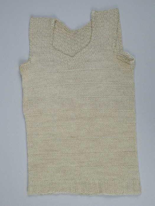 Kinderhemd of borstrok, gebreid van crèmekleurige wol in tricot- en reliëfsteken, blokjespatroon op schouders en langs de hals