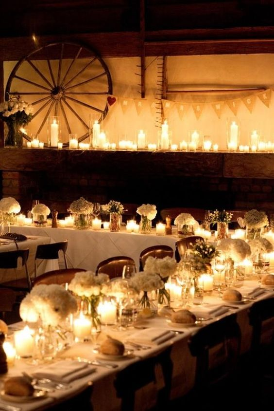 White candles in plain glass vases intermixed with white roses in plain glass vases
