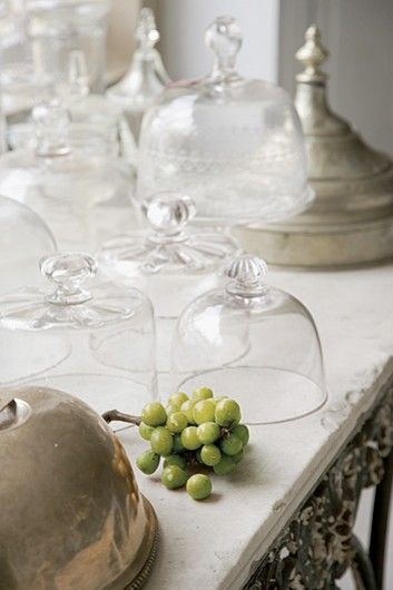Glass cloches and silver on a French pastry table: