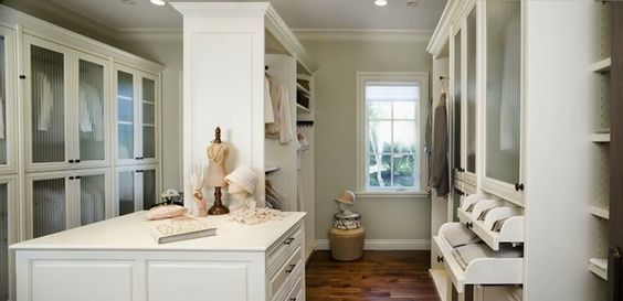 source:Designer Closetswebsite  Gorgeous walk-in closet with central closet island and center closet rails. The closet design features ridged glass fronted closet doors with black hardware. The right hand side of the closet features pull out bin storage as well as clothes rails and shelving. The walls are painted a light gray which complements the creamy white cabinetry. Hardwood floors, baseboards and crown molding complete the space.