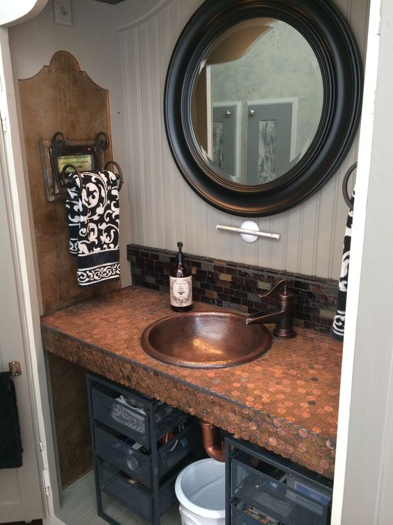 The Husband Vanity Up-cycled armoire turned bathroom vanity. Copper Penny Countertop with copper sink. Interior light-pucks and electric outlets added for shavers.  Chalk paints and fabric decoupage. Doors close to hide the husbands untidiness!