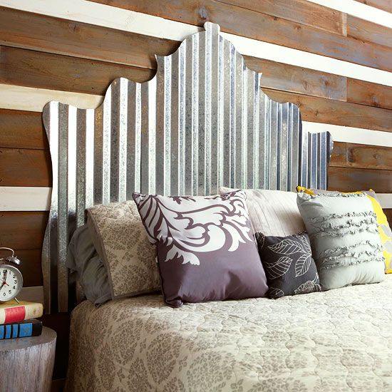 Rustic Bedroom ~ In the guest room, the couple paneled one wall with old fence pickets gifted from a friend. They painted some pickets white to add contrast. The headboard is made from corrugated tin roofing.