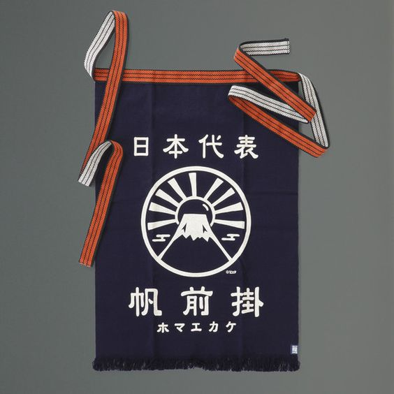 This traditional Japanese apron or 'Maekake', is made in exactly the same way as they were in the Edo period, more that 250 years ago. Genuine Maekake such as this one are only made in Toyohashi City. The cotton fabric is especially woven on a narrow loom in small batches, which gives the apron its distinctive texture. The fringed hem is also a traditional feature. Japanese Maekake aprons are designed to cover the front of the body only.