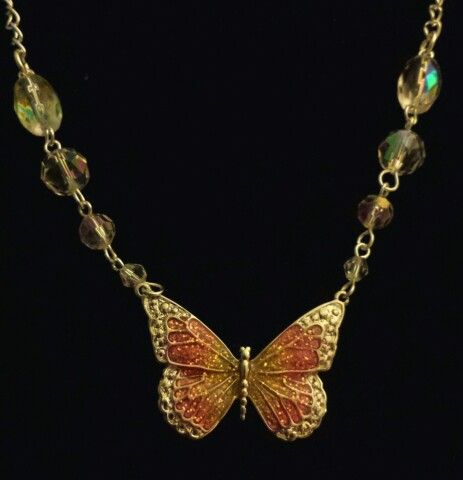 Pink and yellow glitter butterfly pendant with faceted glass beads on a silver chain.