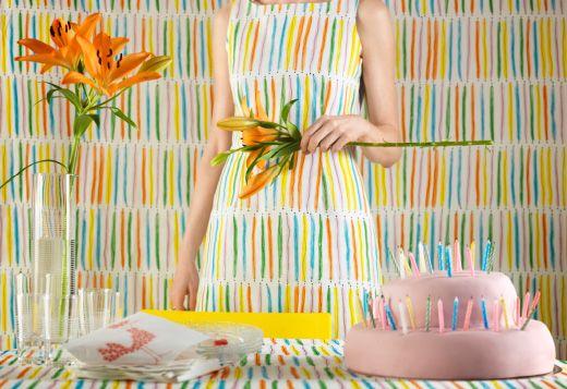 Valkoinen kangas, jossa keltaisia, oransseja, sinisiä, vihreitä ja roosia raitoja.
