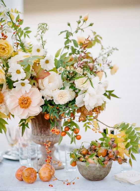 a bright fall wedding centerpiece made with english roses, poenies and ripe fruits #weddingcenterpice #weddinglforals #weddingdesign #fallwedding