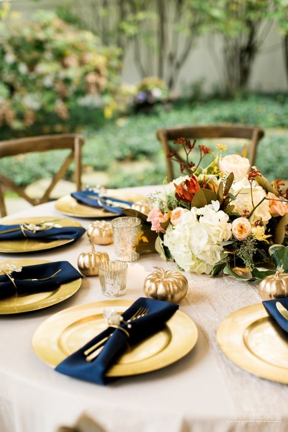 Love the gold charger with navy napkin. The gold and ivory napkin ring is also really pretty. The lace runner is subtle, but so romantic!  Katherine + Weston's fall garden wedding at CJ's Off the Square in Franklin, TN #goldpumpkins