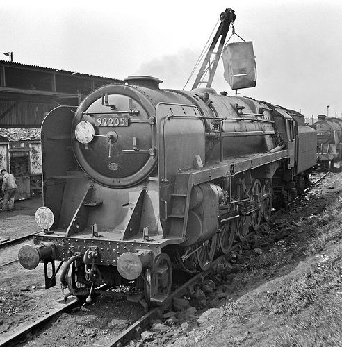 View large. A BR Class 9F is being coaled at Eastleigh in preparation to heading a northbound Fawley to Bromford Bridge oil train. Hampshire, UK. Negative scan.