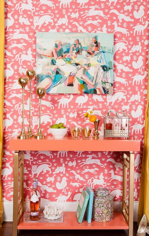 Pink console and wallpaper with brass accessories