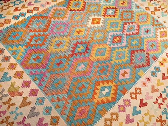 This hand made kilim rug is flat woven in a tapestry weave and made entirely of wool. It is woven by Uzbek weavers in central Afghanistan near the city of Maimana. The archaic designs have changed little over the centuries. However, this newer kilim is made with updated vibrant colors using natural dyes to punch-up…