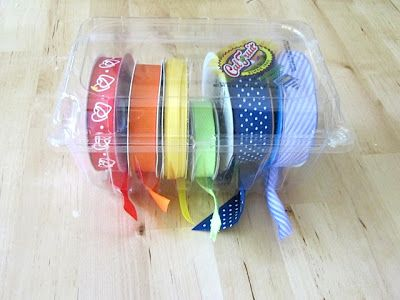this woman never ceases to amaze me with her creativity and organization. She uses strawberry and tomato containers to store her ribbon. The ribbon goes through the ventilation spots at the bottom . So easy, so cheap, so effective. love it.