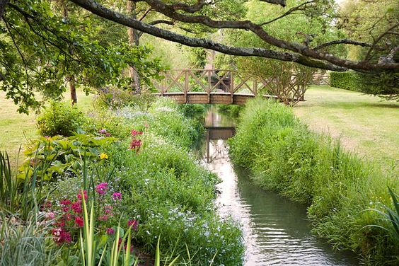 Decorative wooden bridge over stream with naturalistic summer planting including Iris Primula candelabra and Myosoti