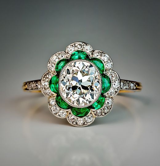 1920s Art Deco Diamond and Emerald Engagement Ring. A superbly crafted platinum topped 18K gold ring centered with a bezel set old cut oval diamond, surrounded by eight petal shaped emeralds, and outlined with a curvaceous border of old cut diamonds.