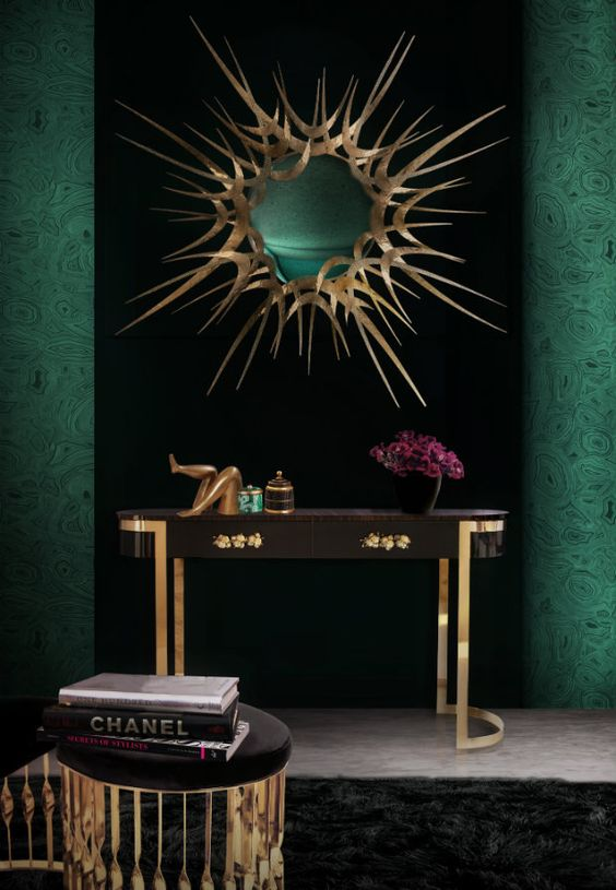 Dramatic deep green walls and modern sculptural gold mirror in bathroom with brass