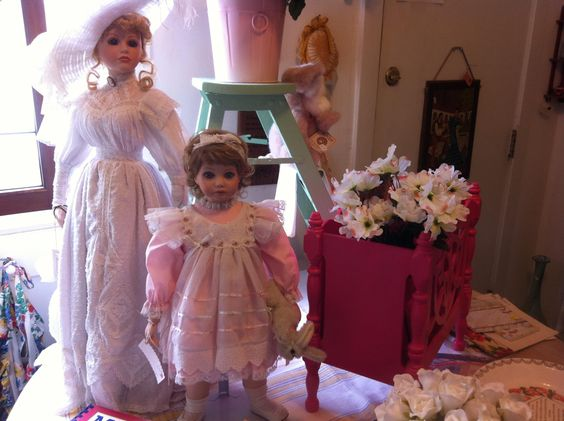 two dolls and a magazine rack