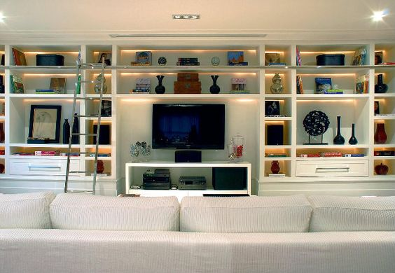 De laca branca, a estante espaçosa ocupa toda a extensão da parede. Ali, cabem de livros ao home theater