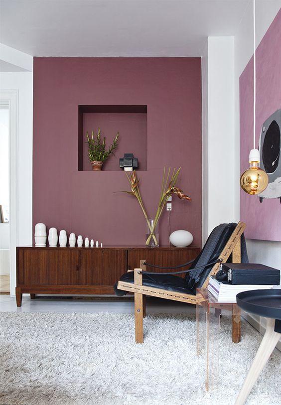Mur rose et meuble en bois foncé