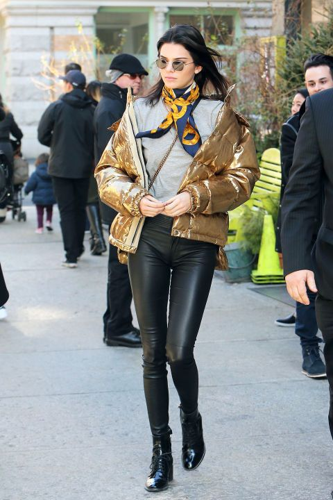 If you were on the fence about the whole puffer coat trend, Kendall Jenner is here to make you a believer. The model went shopping  in NYC with Hailey Baldwin on Monday and bundled up against the chilly temps in a metallic gold down jacket that was just too cool. She paired the statement piece with a casual gray tee and black leather leggings (a model-off-duty staple), then accessorized with black lace-up booties and a printed Chanel neck scarf for a chic vintage touch. Consider us converted to