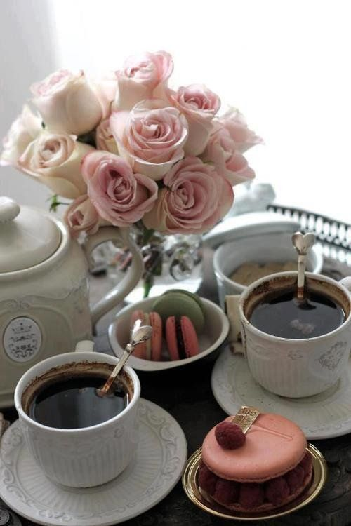 Tasse de thé, macarons, et bouquet de fleurs.