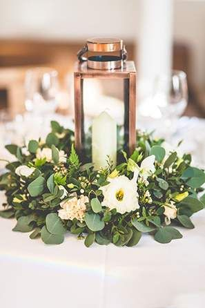 You can also choose traditional low centerpieces likes ones where the flowers are in a box vase, such as the peonies and roses above (left). Or surround a hurricane lamp with a wreath of flowers and greenery.