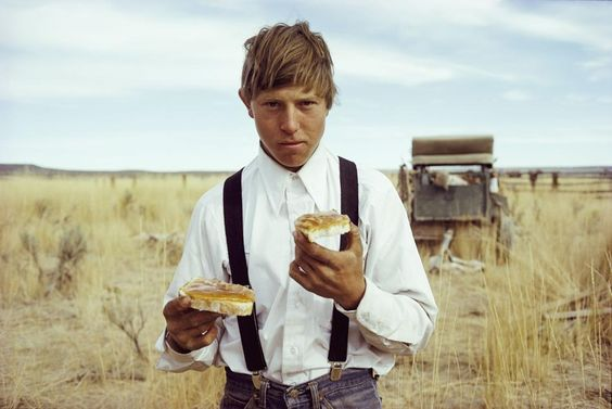 Picture of a young cowboy eating a sandwich