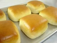 Texas Roadhouse Rolls  4 tsp. active dry yeast  1/2 c. warm water  2 c. milk, scalded and cooled to lukewarm  3 Tbl. of melted butter, slightly cooled  1/2 c. sugar   2 quarts all purpose flour (7-8 cups)  2 whole eggs  2 tsp. salt