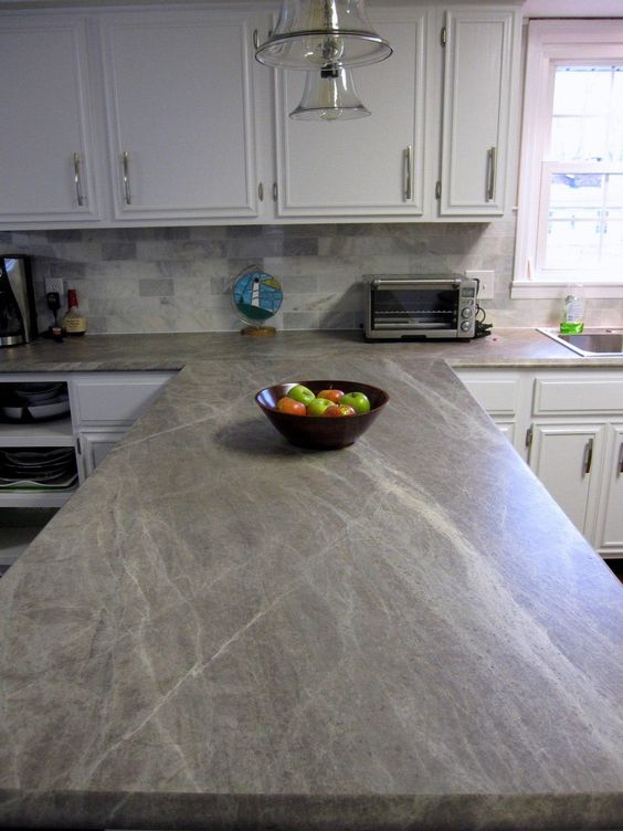 This pale gray soapstone almost blends in with the off-white cabinets and the white streaks running through make it look even more expensive and elegant than it already does.